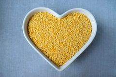 Lentilhas amarelas em uma bacia na forma do coração imagem de stock royalty free