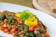 Lentilhas cozidos com espinafres, pimenta e cebola Imagem de Stock