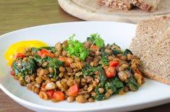 Lentilhas cozidos com espinafres, pimenta e cebola Fotografia de Stock