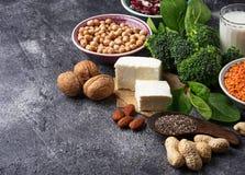 Lentilhas, grão-de-bico, porcas, feijões, espinafres, tofu, brócolis e qui Fotografia de Stock