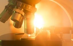 Lentille de microscope avec la lumière orange Photographie stock