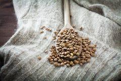 Lentilles au-dessus de cuillère et de laine crus Images stock