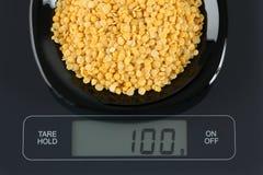 Lentilles fendues de jaune sur l'échelle de cuisine Images stock
