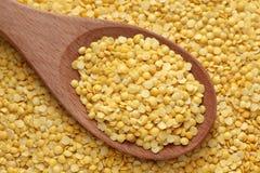Lentilles jaunes dans une cuillère en bois Image stock