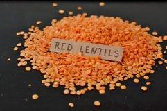 Lentilles rouges avec le label sur le fond noir Photographie stock