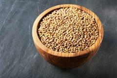 Lentilles sèches dans une cuvette en bois sur une table en bois photo stock