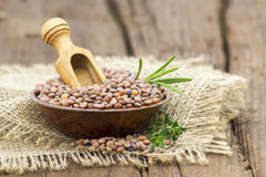 Lentils in a bowl. Wooden background Stock Image