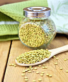 Lentils green in jar and spoon with napkin Stock Photos