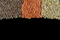 Lentils. Varied dried lentils, on black background with negative space in the low part Stock Image