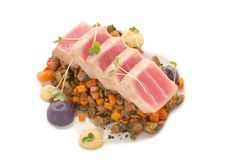 Lentils with vegetables on top of tuna pieces on isolated background. Molecular modern kitchen, lentils with vegetables, pieces of raw tuna with sauce, seasoning Stock Photos