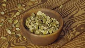 Lento: as sementes de abóbora descascadas caem em um prato de madeira em uma tabela video estoque