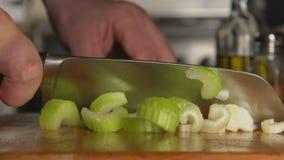 LENTO: La mano di un cuoco taglia un sedano da un coltello video d archivio