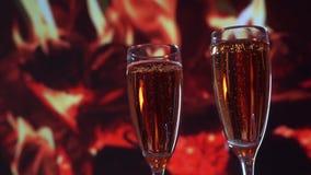 Lento moushen Champán en vidrios de flauta, con una botella enfriándose por el fuego almacen de video
