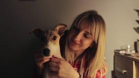 Lento-movimento Conforto e conceito acolhedor A jovem mulher bonita guarda seu cão bonito do terrier de raposa em seus mãos e a d vídeos de arquivo