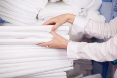 Lenzuola bianche impilate nella stanza di riserva fotografia stock libera da diritti