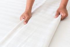 Lenzuolo bianco installato mano nella camera di albergo Immagini Stock