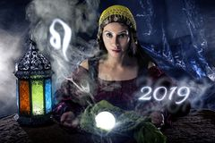 2019 Leo Predictions. Psychic or fortune teller with crystal ball and horoscope zodiac sign of Leo royalty free stock photography