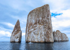 Leon Domidos or Kicker Rock, group of three rocks in Galapagos I. Leon Domidos or Kicker Rock, group of three rocks rising sharply from sea with small boat Stock Photos