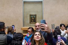 Leonardo Da Vinci`s Mona Lisa at the Louvre Museumn. PARIS, FRANCE - Nov 10, 2017: Visitors do selfie and take photo of Leonardo Da Vinci`s Mona Lisa at the royalty free stock photos