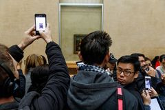 Leonardo Da Vinci`s Mona Lisa at the Louvre Museumn. PARIS, FRANCE - Nov 10, 2017: Visitors do selfie and take photo of Leonardo Da Vinci`s Mona Lisa at the royalty free stock image