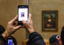 Leonardo Da Vinci`s Mona Lisa at the Louvre Museumn. PARIS, FRANCE - Nov 10, 2017: Visitors do selfie and take photo of Leonardo Da Vinci`s Mona Lisa at the royalty free stock photo