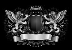 Leones cons alas que sostienen el emblema de la oscuridad del escudo Imágenes de archivo libres de regalías