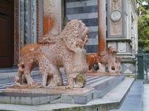 Leones de piedra rojos como camareros en la ciudad italiana Bérgamo Fotos de archivo