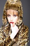 Leopard fur at stylish girl. Look of fashion model with bad taste. Fur coat boutique with natural and artificial. Material. Woman in leopard fur coat isolated stock images