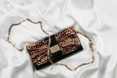Leopard lacquer bag lying on a white silk Royalty Free Stock Photo