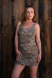 Leopard print dress. Beautiful tall redhead in a leopard print dress royalty free stock image