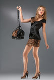 Leopard revolution. A studio portrait of a sexy hot lady in leopard clothes holding a bag Royalty Free Stock Images