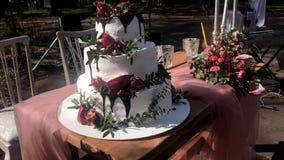 LEOPOLI, UCRAINA - 14 APRILE 2019: Bella tavola decorativa di nozze con le candele, i fiori e un dolce di tre-strato di bianco stock footage