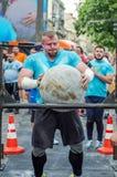 LEOPOLI, UCRAINA - GIUGNO 2016: Le forti maciste del culturista sollevano una palla di pietra pesante enorme fatta di marmo e la  Fotografia Stock