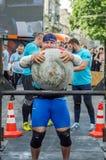 LEOPOLI, UCRAINA - GIUGNO 2016: Le forti maciste del culturista sollevano una palla di pietra pesante enorme fatta di marmo e la  Fotografie Stock