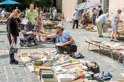 Leopoli, Ucraina - luglio 2015: Gli uomini e le donne scelgono e affare ed i venditori stanno vendendo i vecchi libri rari e gli  Fotografia Stock Libera da Diritti