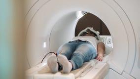 Leopoli, Ucraina - 15 maggio 2018 Donna che si trova sull'analizzatore di RMI o di CT, sistema diagnostico di radiologia, esame m video d archivio