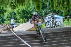 LEOPOLI, UCRAINA - MAGGIO 2016: Lo sportivo su un casco della bicicletta sta correndo all'alta velocità che rimbalza la concorren Fotografia Stock Libera da Diritti