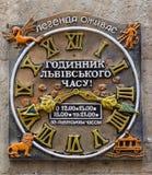 Leopoli, Ucraina - novembre 2015: Vecchie retro ore d'annata della scultura del monumento sulla casa a Leopoli Fotografia Stock