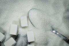 Lepel in een stapel van suiker en suikerkubussen naast royalty-vrije stock afbeeldingen