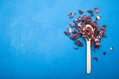 Lepel en verspreide hibiscus op een blauwe achtergrond De ruimte van het exemplaar stock afbeeldingen