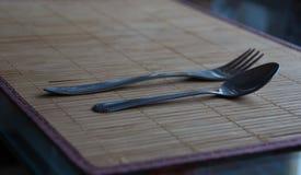 Lepel en vork die op een bamboemat liggen stock foto's