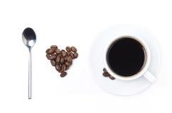 Lepel, kop zwarte koffie en koffiebonen in de vorm van hart Stock Afbeelding