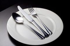 Lepel, Mes en vork op een witte plaat Stock Afbeeldingen