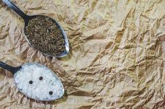 Lepel met overzeese zout en zwarte peper en een lepel met zaden van komijn op een het bewerken document stock fotografie
