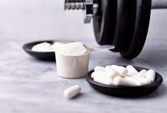 Lepel van Weiproteïne, Creatine, Taurine capsules en een domoor stock fotografie