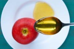 Lepelhoogtepunt van Honing over appel en honingsplaat Stock Foto