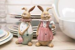 Lepre delle terraglie di due Pasqua su uno scaffale del tavolo da cucina Figurine ceramiche per il servizio della tavola festiva  fotografie stock