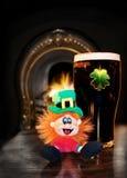 Leprechaun de San Patricio con la cerveza irlandesa negra Fotos de archivo