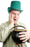Leprechaun Excited by Pot of Gold. Irish man dressed as leprechaun, excited to be getting a pot of gold coins.  White background Stock Photo