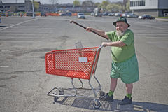 The Leprechaun goes shopping. A man living the life of a leprechaun pushes an orange shopping cart in the parking lot of a supermarket Royalty Free Stock Photography